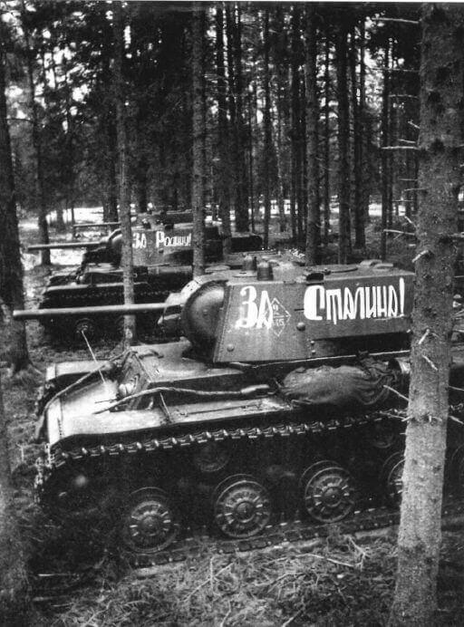 "KV-1 tanks in the forest before the battle. Western Front, 116th tank brigade, April 1942. [The inscriptions are ""For Homeland!"" on the far one and ""For Stalin!"" on the near one.]"